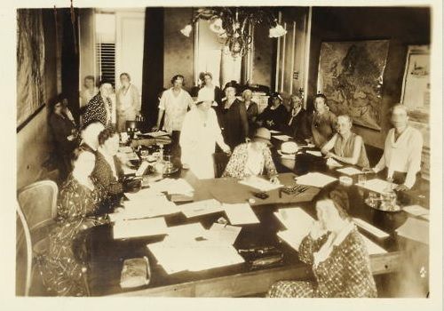 """1931 Doris Stevens working with Women's Consultative Committee at League of Nations, ca. 1931. Alice Paul is standing behind Stevens in the center."""""""